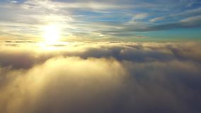 Amazing aerial helicopter drone shot flight over white rain fluffy clouds in blue sky evening sunset sunshine cloudscape