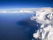 Spectacular aerial view from airplane window, beautiful, unique and picturesque white clouds with deep blue sky background Royalty Free Stock Photo