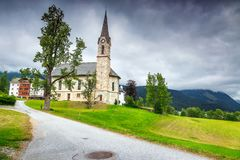 Summer alpine landscape with traditional church and green fields, Austria Stock Image