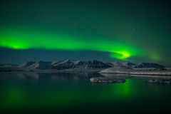 Spectacular auroral display over the ice lagoon Jokulsarlon, Iceland. Spectacular green auroral display over the ice lagoon Jokulsarlon, Iceland Stock Photo