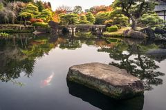 Spectacular autumn foliage and a bridge over the pond at Koko-en Gardens in Himeji, Japan. Spectacular autumn foliage reflected in the water and the classical royalty free stock photo