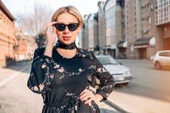Beautiful cute blonde model in dress posing in the city stock photos