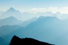 Spectacular blue and cyan mountain ranges silhouettes. Summit crosses visible. Stock Image