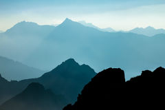 Spectacular blue and cyan mountain ranges silhouettes. Summit crosses visible. Stock Photos