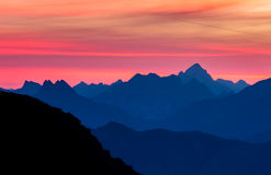 Spectacular blue mountain ranges silhouettes and pink violet clouds Royalty Free Stock Photography