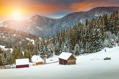 Amazing winter sunset with snowy rural wooden chalets, Transylvania, Romania stock photography