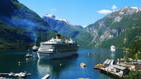 Spectacular clip of Geiranger Fjord and mountains with snow and waterfalls and cruiseliners and ferry boats carrying tourists. Spectacular clip of Geiranger stock video footage