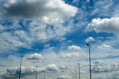 Spectacular Clouds & Receding Light Poles. Vibrant cotton candy-like clouds fill the sky and a series of street light poles recede into the distant horizon stock image