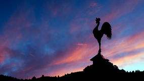 Spectacular dawn with cockerell weathervane and landscape. Red s Stock Photos
