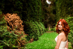 Spectacular glance of the redhead bride. In the park Royalty Free Stock Photo