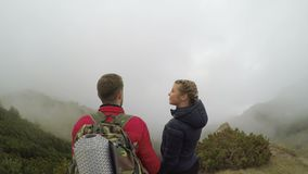 Mountain landscape full of floating mist admired by young couple of tourists holding hands and kissing tourism concept -. Spectacular high view of mountain stock footage