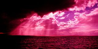Dark threatening cloudy sunrise over ocean with pink crepuscular. A spectacular hot pink sunbeams sunrise over tropical water with brightly colored crepuscular Royalty Free Stock Images