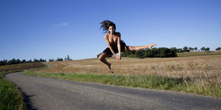 Spectacular jump of a woman over a country road. Royalty Free Stock Photography