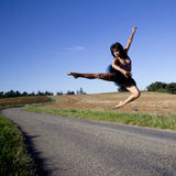 Spectacular jump of a woman over a road. Royalty Free Stock Photography