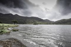 Spectacular lighting condition in Lake District,Cumbria,Uk. Dramatic sky with dark clouds over mountain lakeshore opens and hits lake surface with light stock photos