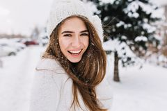 Spectacular long-haired woman laughing while posing on snow background. Outdoor close-up photo of caucasian female model. With romantic smile chilling in park royalty free stock photo