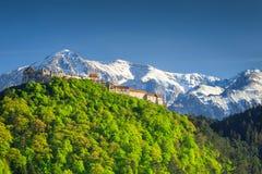 Spectacular medieval citadel in Rasnov city, Brasov region, Transylvania, Romania. Amazing spring landscape with Rasnov fortress and high snowy Bucegi mountains stock photo