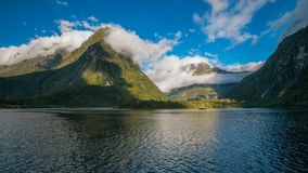 Spectacular Milford Sound mountain range surrounded by clouds close to sunset. Spectacular mountain range surrounded by clouds close to sunset at Milford Sound Stock Image