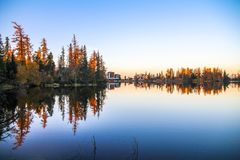 Spectacular Mountain lake Strbske pleso Strbske lake with mirror reflection of trees in lake at sunrise royalty free stock images