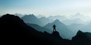 Spectacular mountain ranges silhouettes. Man reaching summit enjoying freedom. Happy winning success man at sunset or sunrise standing relaxed and is happy for Royalty Free Stock Photo