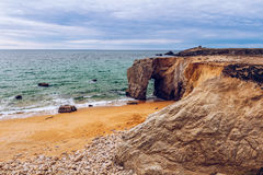 Spectacular natural cliffs and stone arch Arche de Port Blanc an Royalty Free Stock Photos