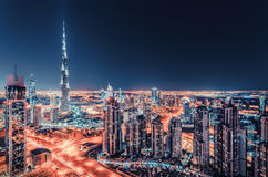 Spectacular nighttime Dubai skyline with illuminated skyscrapers. Stock Photos