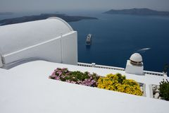 spectacular panoramic sea front view with white roof, yellow and pink flower and a blu sea with cruise ships anchored stock photo