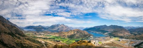 Queenstown Scenic Alpine Panorama in summer. Spectacular Panoramic Views of Lake Wakatipu and the Mountain range surrounding Queenstown city and airport with Royalty Free Stock Image