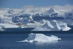 Spectacular Ice Landscape in Antarctica. This spectacular photograph shows the texture of blue icebergs, with the surrounding mountains on a bright sunny day in stock image
