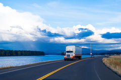 Spectacular river view of road with semi truck and trailer. Semi-Truck and trailer with combined colors white and orange with lights on delivers goods to local Stock Image