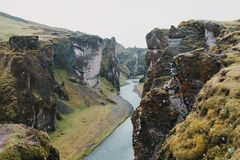 Spectacular rocky mountains with green vegetation and small river. In fjadrargljufur, iceland stock image