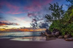 Spectacular romantic purple sunset at anse georgette, praslin, seychelles 2. Spectacular romantic purple and orange colored sunset on paradise beach with granite stock photos