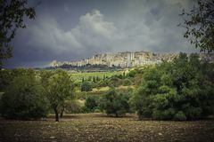 Spectacular scenic view of Agrigento and the seculiar olive trees from the Valley of the temples in Sicily. On a menacing cloudy summer day royalty free stock images