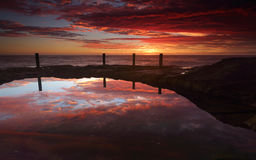 Spectacular sunrise over Ivo Rowe Rockpool Coogee Australia. Spoilt this morning with a spectacular sunrise full of vivid colours painting the sky with reds and royalty free stock photography