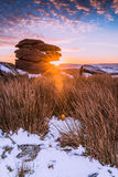 Spectacular sunrise on rocky hill mountain at snowy morning Stock Image