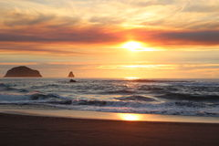 Spectacular Sunset Oregon coast Pacific ocean. Super gorgeous sunset over the pacific west ocean of the Oregon Coast. Sun is reflecting onto the ocean waves Stock Photo
