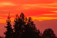 A spectacular sunset over the mountains paints the sky of pink, orange and yellow. The sun was very low beyond  the horizon and its rays crossing the atmosphere Royalty Free Stock Photos