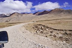 Spectacular View of the gigantic mountain range Kanchenjunga and the rugged barren road leading to Gurudongmar Lake stock photography