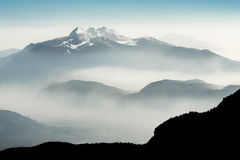 Spectacular view of mountain ranges silhouettes and fog in valleys. Royalty Free Stock Photos
