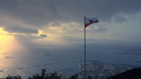 Spectacular view from the Rock of Gibraltar to waving flag of Gibraltar the sea below stock footage