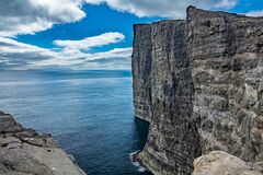 Sorvagsvatn lake cliffs over the ocean with tourists, Faroe Islands
