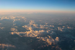 Spectacular view of a sunset above the clouds from airplane wind Royalty Free Stock Photo