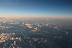 Spectacular view of a sunset above the clouds from airplane wind Stock Photos