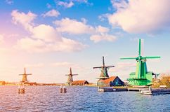 Spectacular view of the water and windmills in Zaanse Schans, Ho. Lland, Europe against the backdrop of a cloudy sky at sunset royalty free stock image