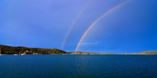 Spectacular vivid Double Rainbow photo in blue sky. Stock Photo