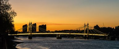 Albert Bridge Sunset in London. Spectacular, warm and vibrant sunset colors in front of a Albert bridge in Battersea park, London stock photo