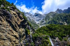 Spectacular waterfall in Milford Sound fiord. Royalty Free Stock Image