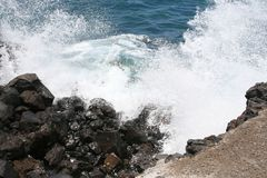 Spectacular waves at volcanic rocks in the ocean Stock Image