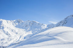Spectacular winter scenery with mountain range. Spectacular winter scenery with high mountain range covered by white snow shining in the sunlight, under a clear royalty free stock photo