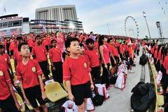 Spectateurs chantant au Singapour l'hymne national pendant la répétition 2013 du défilé de jour national (NDP) Photo libre de droits